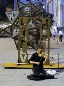 Pietrasanta, Piazza Duomo, un musicista di strada e un opera di Jan Fabre (2011) (foto Giorgio Pagano)